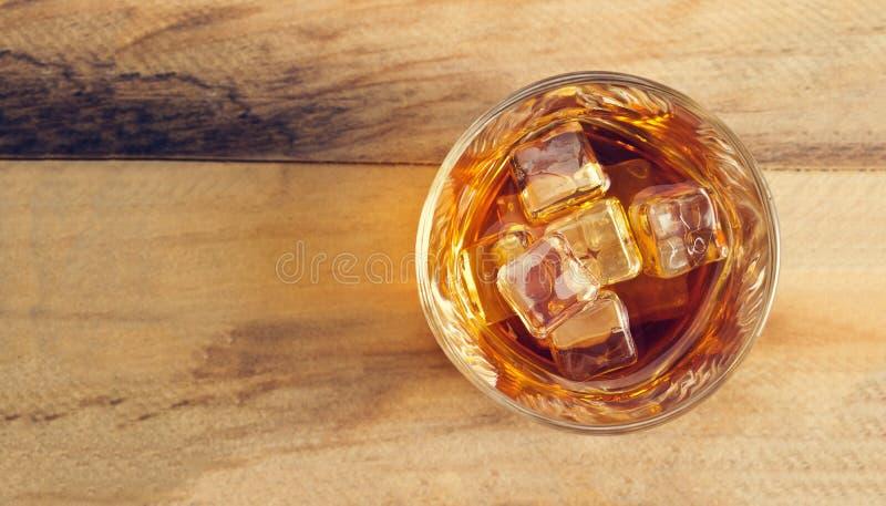 Vidro do uísque com gelo no fundo de madeira, vista superior foto de stock