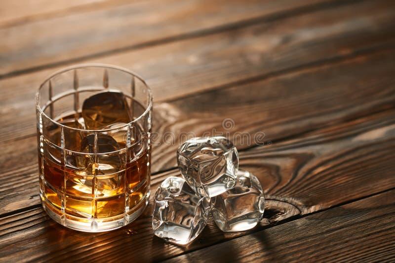 Vidro do uísque com os cubos de gelo na tabela de madeira fotografia de stock
