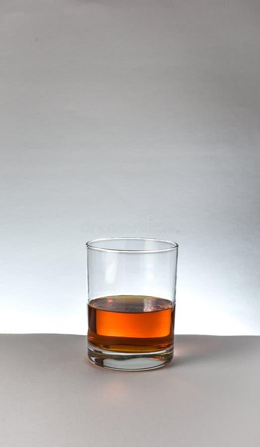 Vidro do uísque de bourbon na superfície do branco imagens de stock royalty free