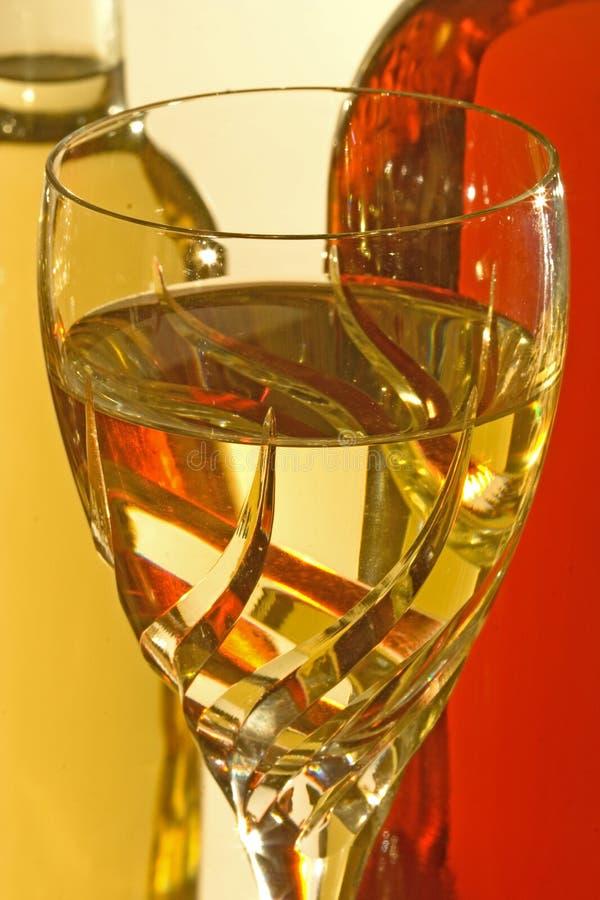 Vidro do vinho branco com frascos de vinho fotografia de stock