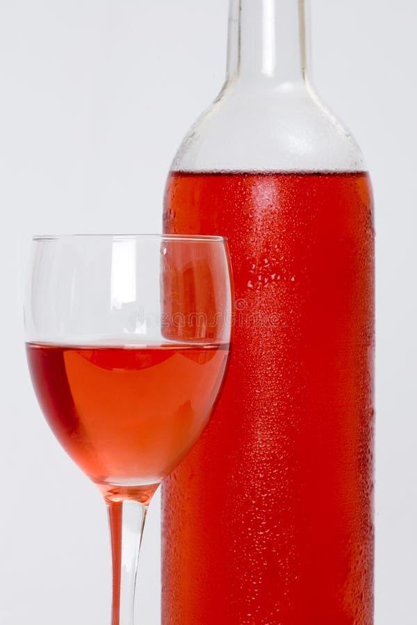 Vidro Do Vinho Cor-de-rosa Com Frasco E Fundo Branco Fotografia de Stock Royalty Free