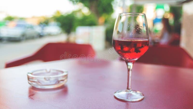 Vidro do vinho cor-de-rosa na tabela em tonificação Defocused do vintage da imagem do café da rua fotografia de stock