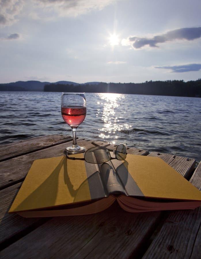 Vidro do vinho, do livro, e dos vidros no lago imagem de stock royalty free