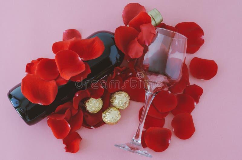 Vidro do vinho e da garrafa nas pétalas cor-de-rosa e nos chocolates Dia do `s do Valentim fotos de stock royalty free