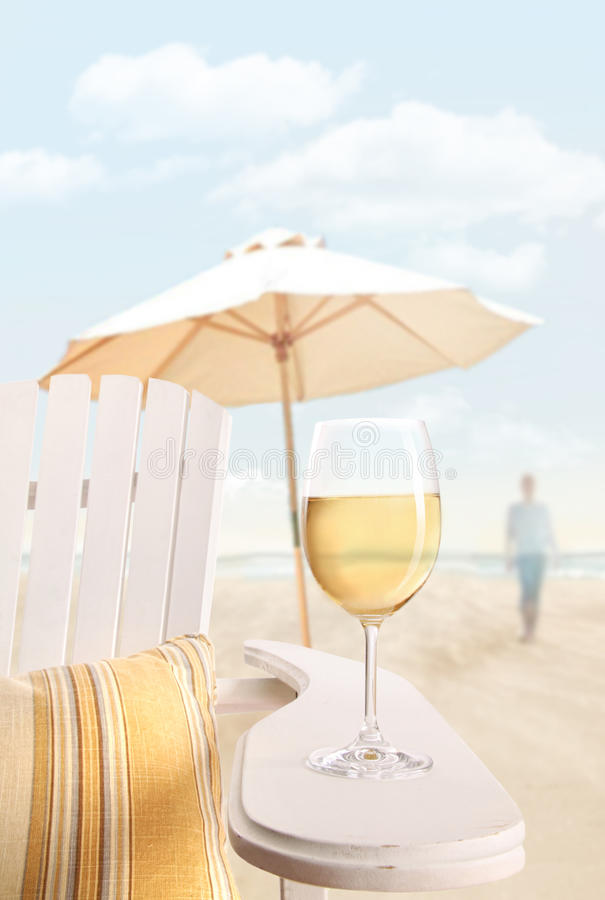 Vidro do vinho na cadeira do adirondack na praia fotografia de stock