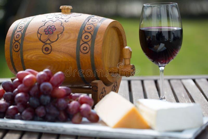 Vidro do vinho tinto com as uvas na tabela de madeira foto de stock