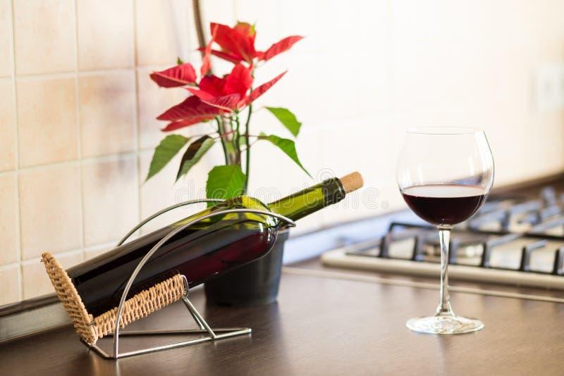 Vidro do vinho tinto com a garrafa no worktop da cozinha imagens de stock royalty free