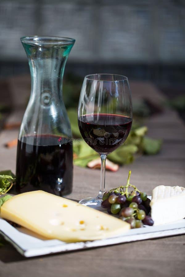 Vidro do vinho tinto, com garrafa, queijo e uvas imagem de stock