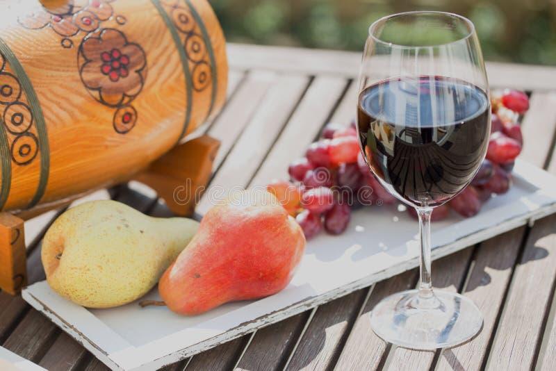 Vidro do vinho tinto com queijo e uvas na tabela de madeira imagem de stock