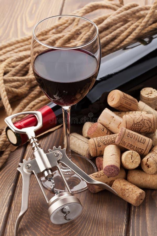 Vidro do vinho tinto, da garrafa, do montão das cortiça e do corkscrew fotos de stock