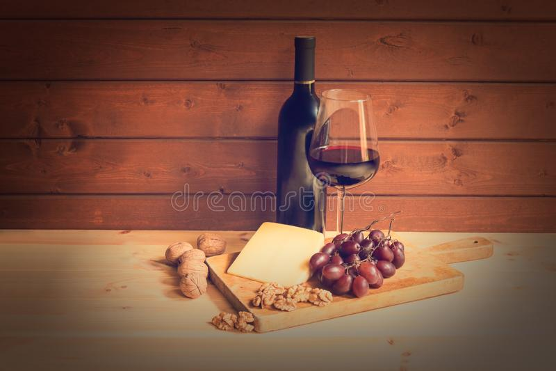 Vidro do vinho tinto, da garrafa do vinho, do queijo parmes?o, das nozes e de uvas vermelhas Imagem tonificada fotografia de stock
