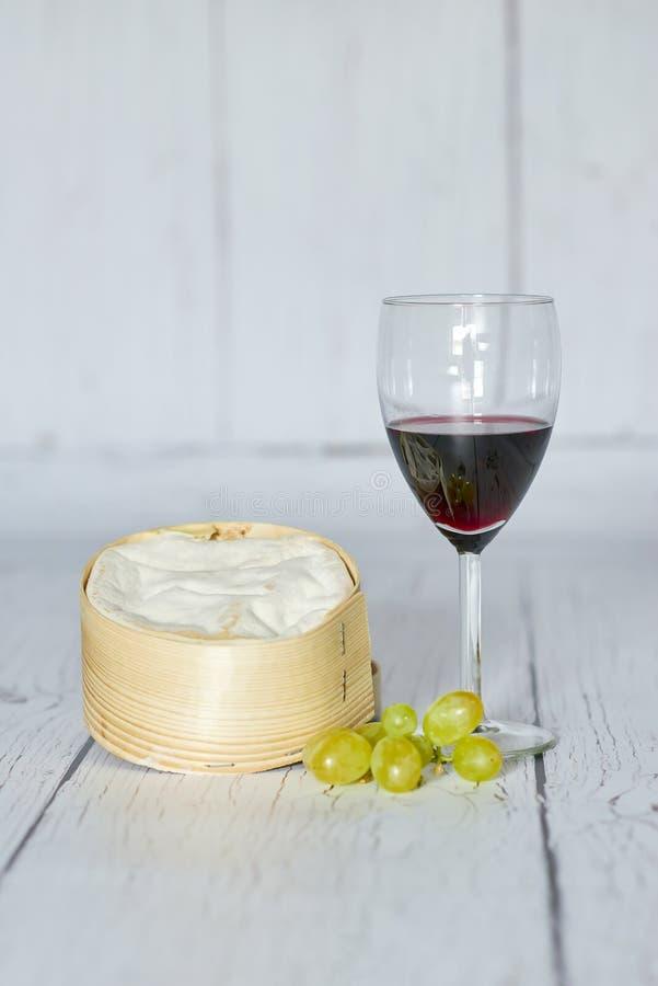 Vidro do vinho tinto, das uvas brancas e do queijo do camembert na caixa de madeira - vertical foto de stock