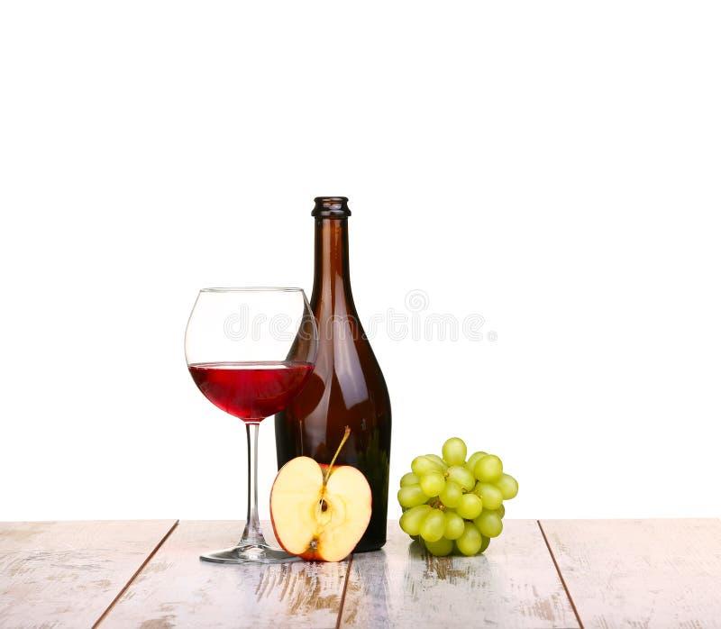 Vidro do vinho tinto, de uma garrafa do vinho e da maçã das uvas a bordo isolada no branco fotos de stock