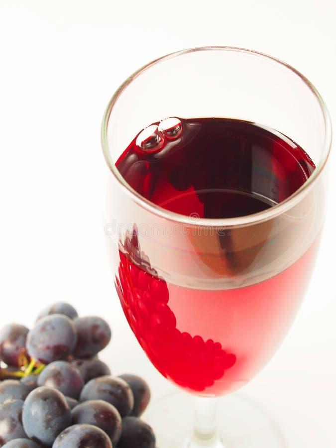 Vidro do vinho tinto e de uvas escuras imagens de stock royalty free