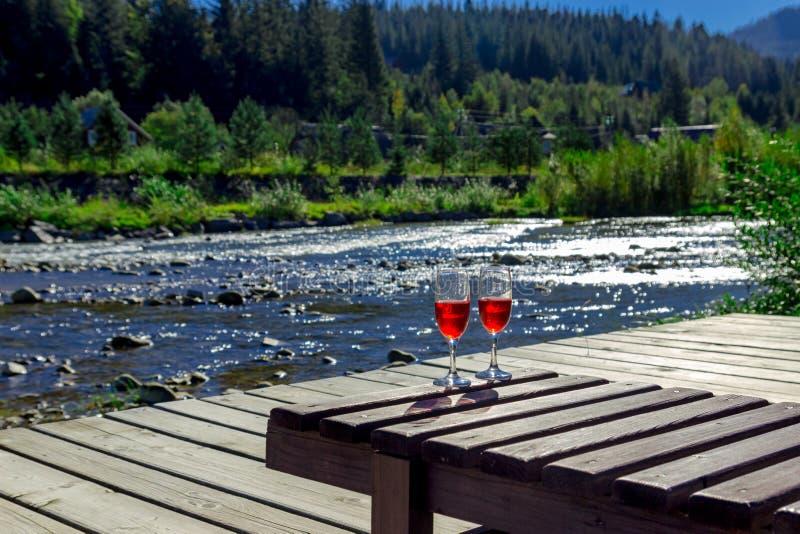 Vidro do vinho tinto no fundo de um rio da montanha Sala de estar de madeira do chaise, montanhas, feriado luxuoso imagem de stock royalty free