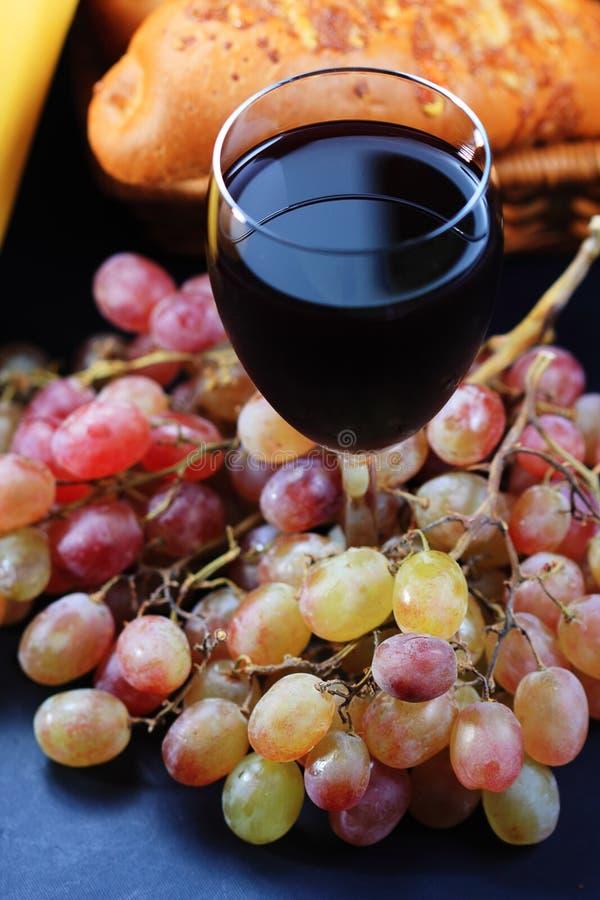 Vidro do vinho vermelho coberto com as uvas fotos de stock