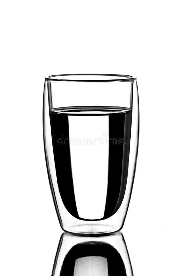Vidro dobro oval transparente com água em um fundo branco imagens de stock royalty free