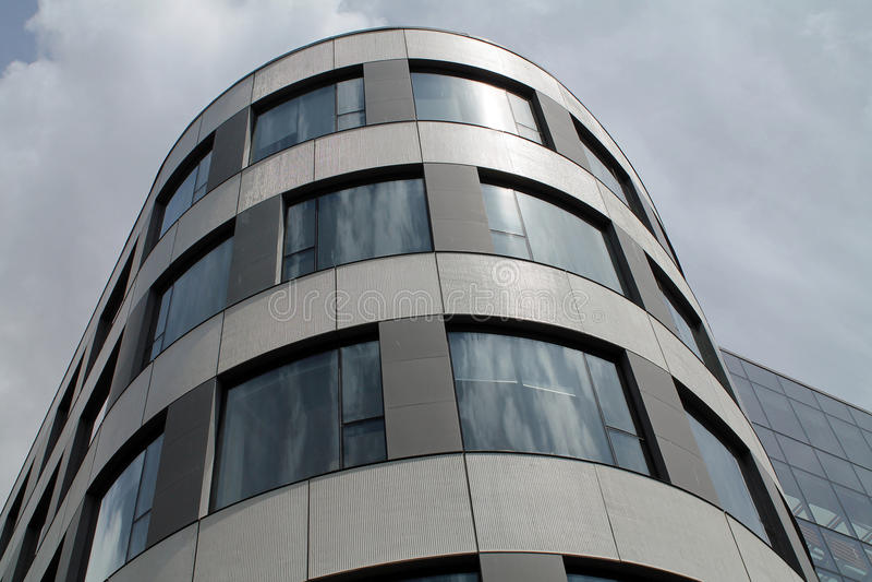 Vidro e exterior curvado aço de um prédio de escritórios do centro fotografia de stock
