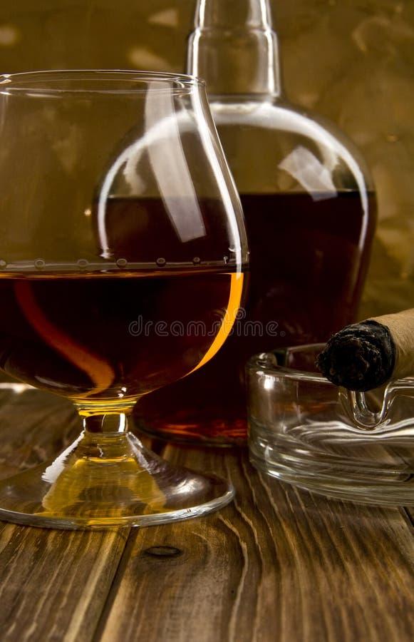 Vidro e garrafa com um charuto imagens de stock royalty free