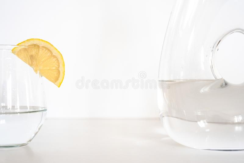 Vidro e garrafa da água com fatia do limão foto de stock