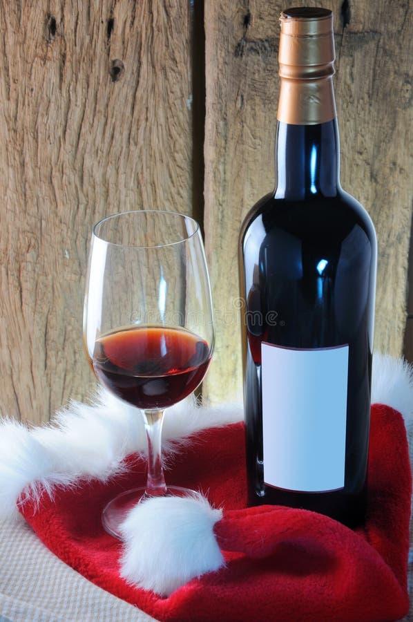 Vidro e garrafa de vinho com o chapéu vermelho de Santa no fundo de madeira fotografia de stock royalty free