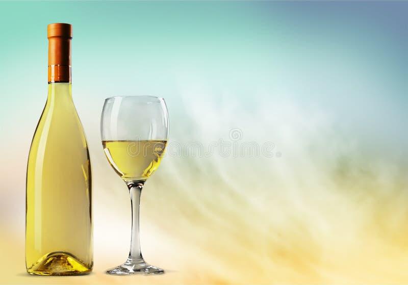 Vidro e garrafa do vinho branco no fundo claro imagens de stock