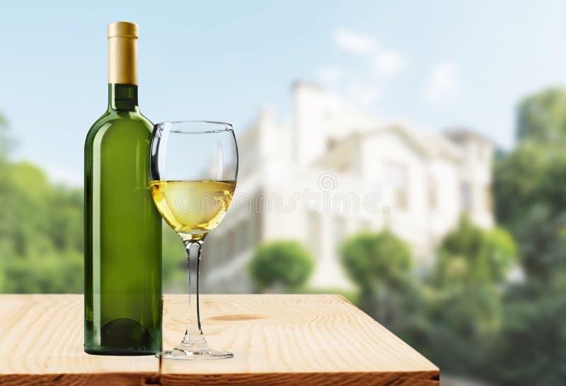 Vidro e garrafa do vinho branco no grunge fotos de stock