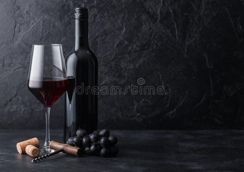 Vidro e garrafa elegantes do vinho tinto com cortiça e do corkscrew no fundo de pedra preto Luz natural imagem de stock