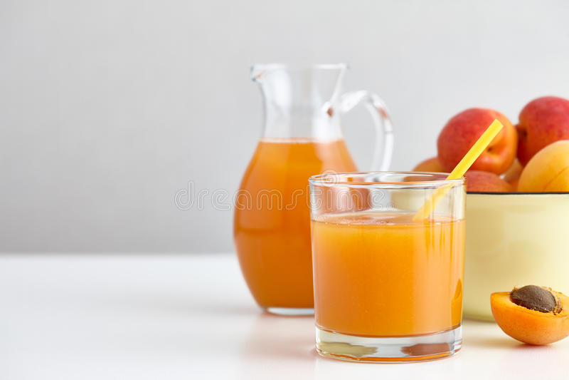 Vidro e jarro de suco fresco do abricó na tabela branca fotografia de stock royalty free
