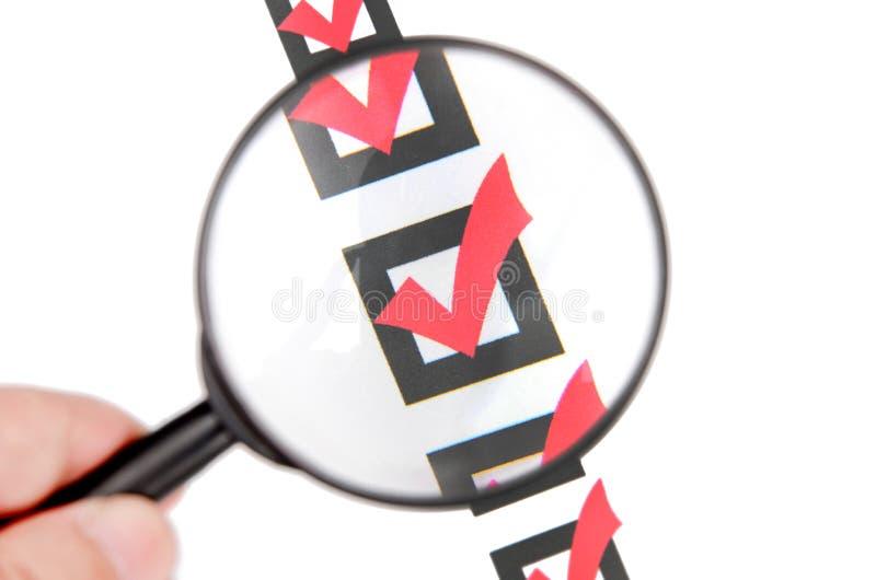 Vidro e lista de verificação da lente de aumento fotos de stock