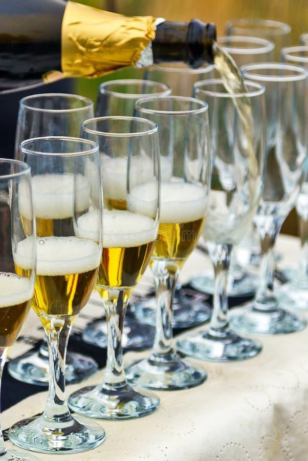 Vidro efervescente de Champagne da garrafa com mais vidros imagens de stock
