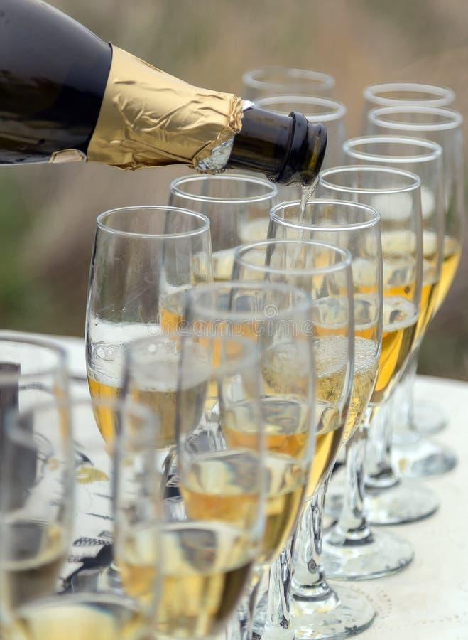 Vidro efervescente de Champagne da garrafa com mais vidros imagens de stock royalty free
