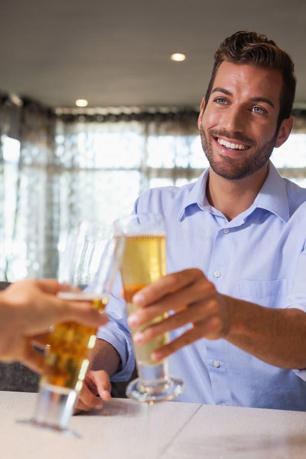 Vidro feliz do tinido do homem de negócios da cerveja com barman fotos de stock royalty free
