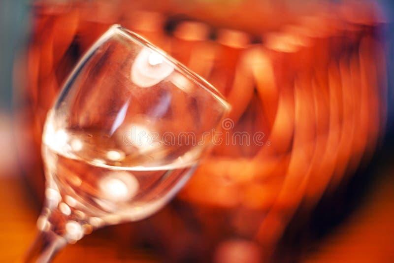Vidro inclinado com um líquido e reflexões em uma cesta de vime borrada do fundo fotografia de stock royalty free