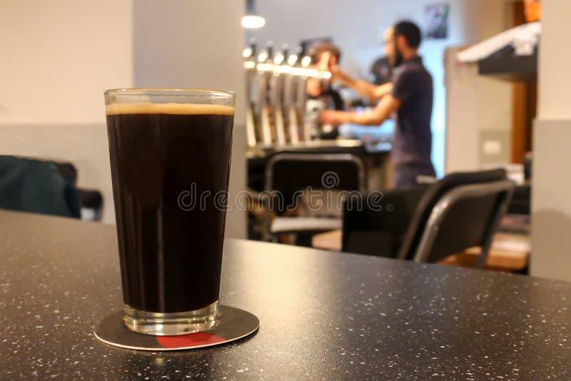 Vidro 0 5 litros da cerveja escura em uma barra da cerveja do ofício fotografia de stock