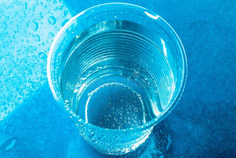 Vidro ou copo plástico descartável com água clara fresca no fundo azul brilhante, vista superior imagem de stock royalty free