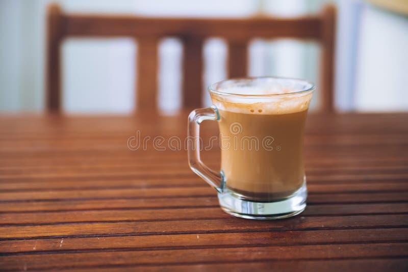 Vidro ou xícara de café com espuma branca na tabela de madeira marrom no balcão, com a cadeira de madeira no fundo, com espaço da imagens de stock royalty free