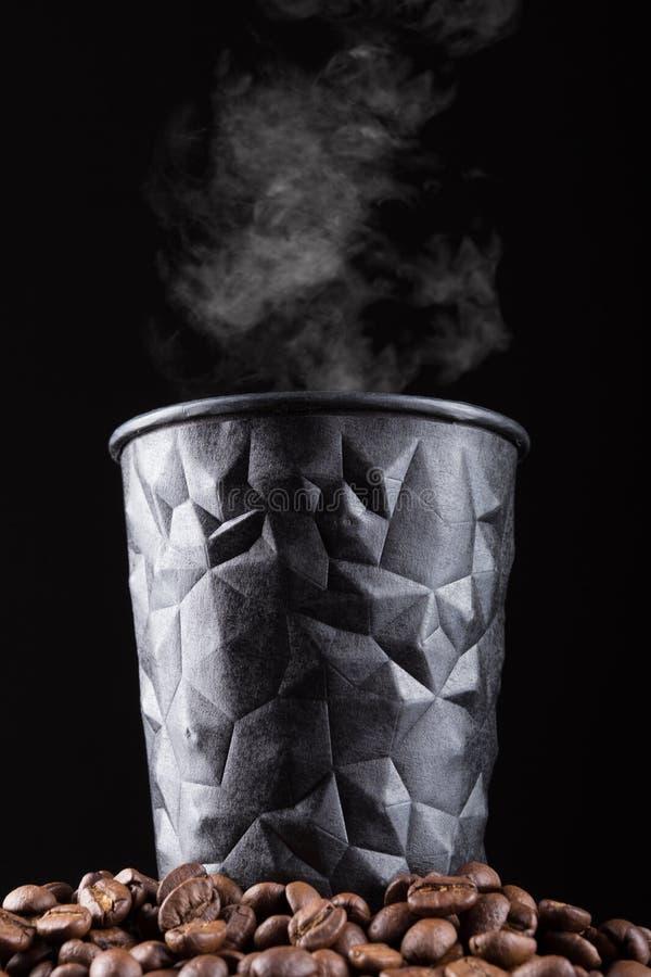 Vidro preto do cartão do café com o vapor que está em uma pilha de feijões de café, conceito de uma bebida do café fotografia de stock royalty free