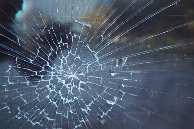 Vidro quebrado Incidente criminoso na parada do ônibus Furo e quebras no vidro de uma parada do ônibus da cidade Textura de vidro fotos de stock royalty free