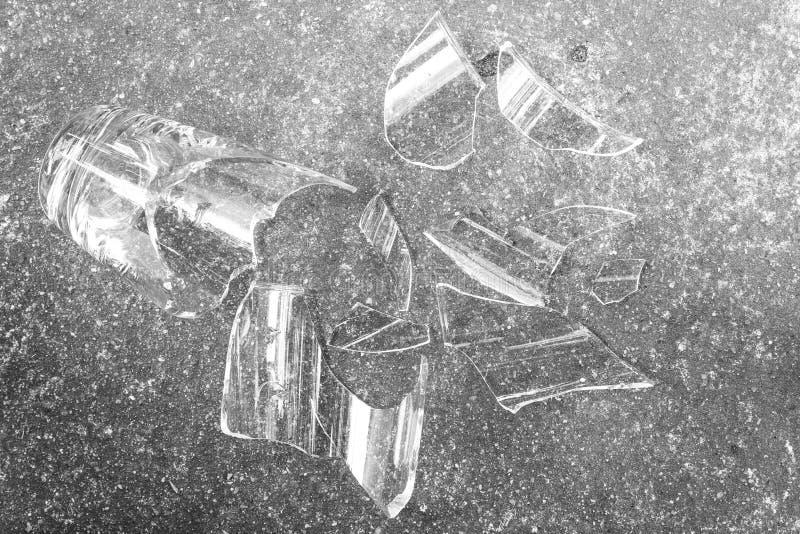 Vidro quebrado no assoalho do cimento imagem de stock