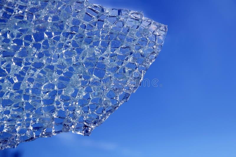 Vidro quebrado rachado sobre o fundo azul fotos de stock royalty free