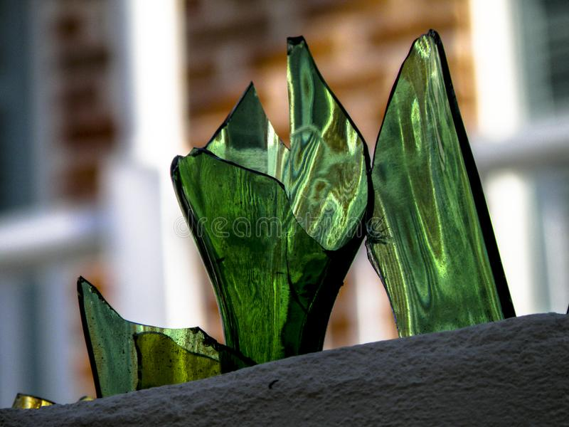 Vidro quebrado usado como a segurança sobre uma parede no bairro francês em Nova Orleães fotos de stock