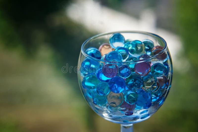 Vidro transparente com bolas do gel em uma obscuridade - fundo verde imagens de stock