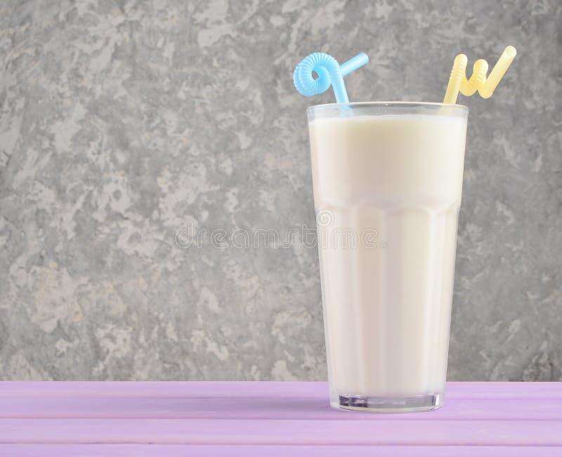 Vidro transparente com leite orgânico fresco, tubules do cocktail em uma tabela de madeira da cor pastel no fundo de um muro de c foto de stock