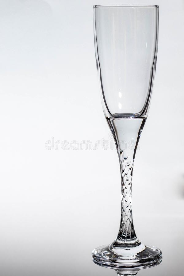 Vidro transparente do champanhe em um fundo branco com o luminoso em ambos imagens de stock