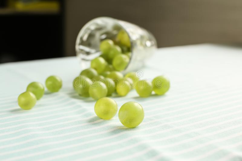 Vidro virado com as uvas dispersadas na tabela fotografia de stock royalty free