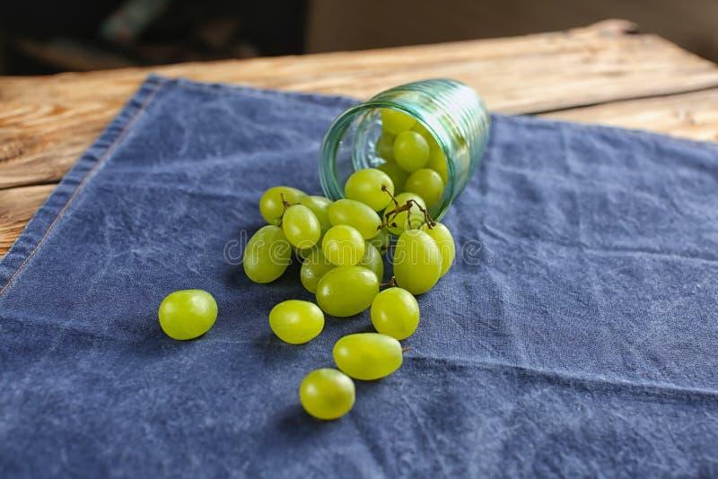 Vidro virado com as uvas dispersadas na tabela foto de stock
