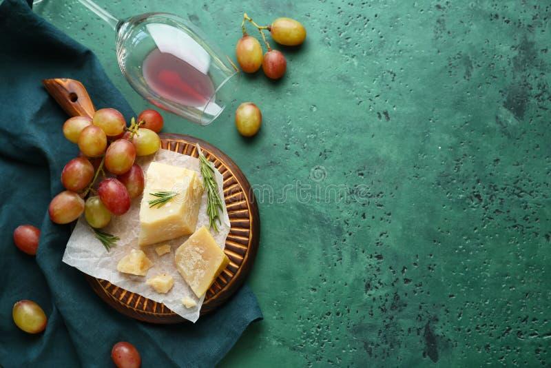 Vidro virado com queijo e as uvas frescas na tabela de cor imagens de stock royalty free