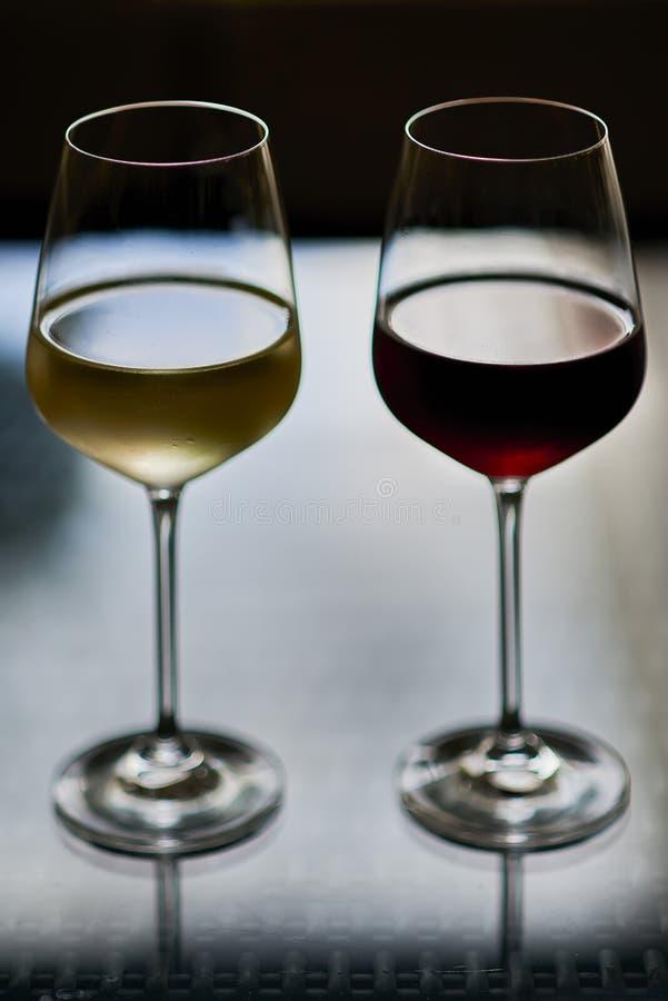 Vidros altos do vinho vermelho e amarelo contra o fundo preto imagens de stock