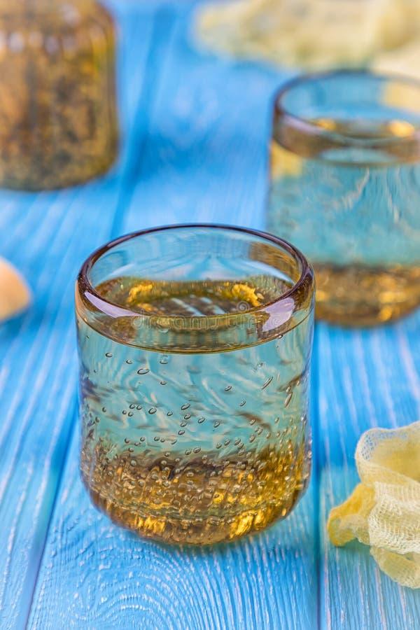 Vidros amarelos com água em um fundo azul foto de stock royalty free